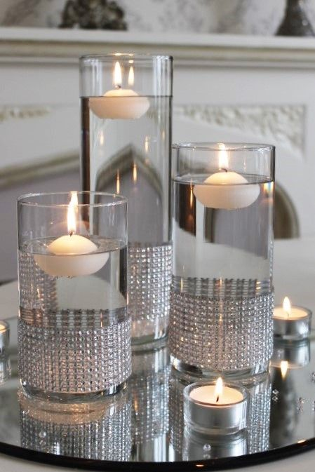 Set of cylinder vases with diamante bands and placed on a mirror .