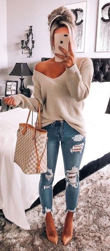 Cute off the shoulder knit sweater with trendy distressed denim .
