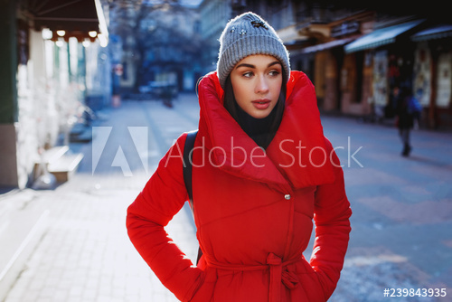 Cute pretty woman look across the christmas street wearing red .