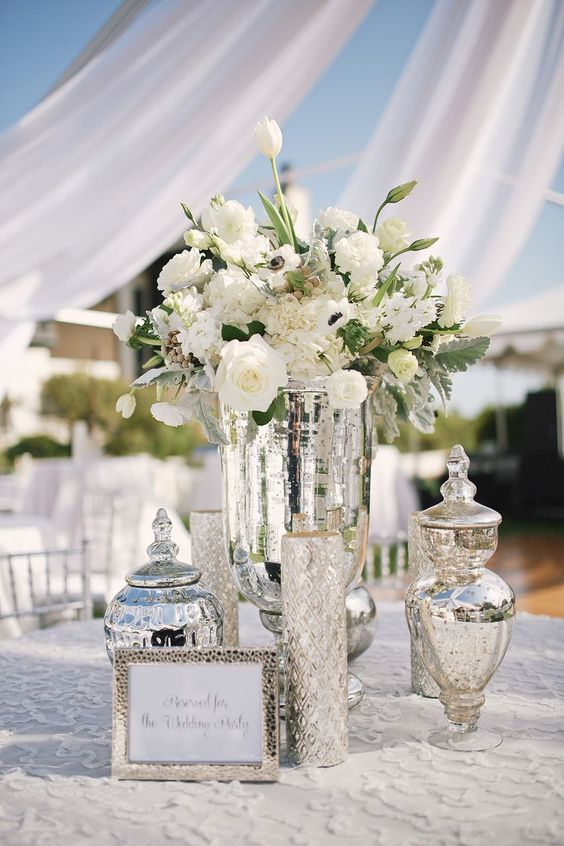 Picture Of mercury glass vases and jars plus white blooms compose .
